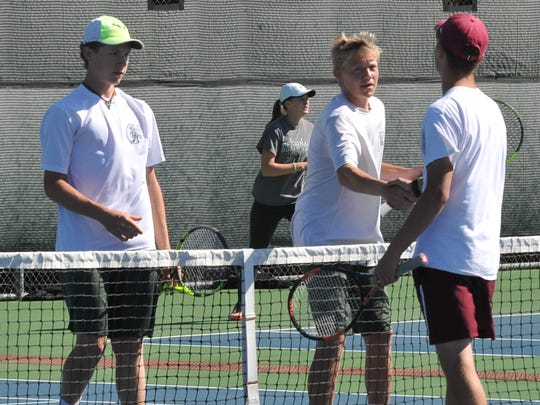 Iowa Park High School tennis players (left) Kody Wells and Cuay O'Conner shake hands with Vernon High School tennis player Ethan Cutis after Iowa Park won the doubles match in a tie breaker 6-2, 7-6 (6)