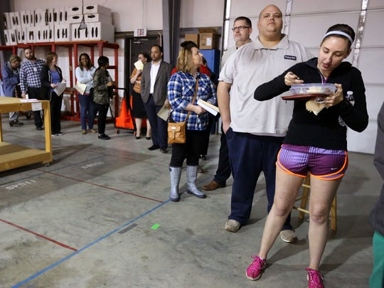 Morgan Lyles, far right, eats dinner, that was delivered to her by her mother while Lyles waits in a long line to vote at the Rutherford County Election Commission Annex on Vine Street, Tuesday, March 1, 2016.