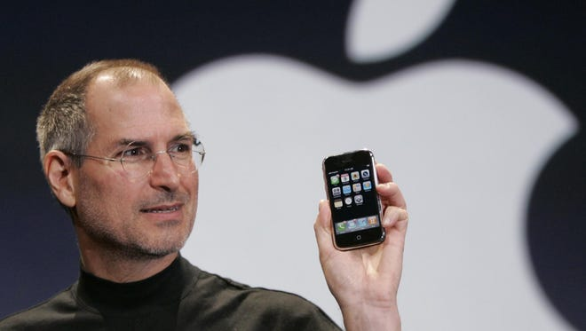 Apple CEO Steve Jobs holds up an Apple iPhone at the MacWorld Conference in San Francisco on Jan. 9, 2007. The phone was launched June 29 that year.