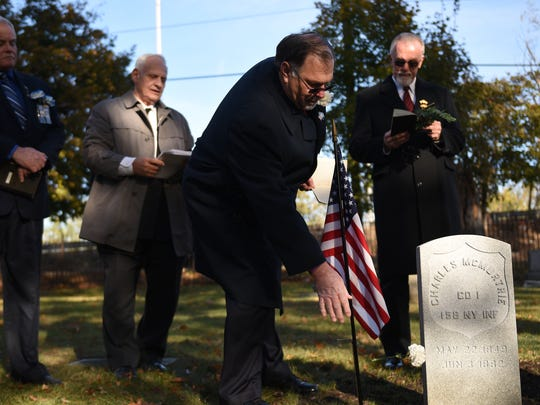 A memorial service at Cedar Lawn Cemetery in Paterson on Saturday November 11, 2017. The service is held as a marker is put on the grave of Charles McMurtrie, a Civil War veteran from Paterson who died in the 1880s and whose grave had been unmarked until his great great granddaughter, Maureen Clary of SC, tracked down his existence and history. Richard Roesch, PGS from the Improved Order of the Red Men, places a white flower on the grave.