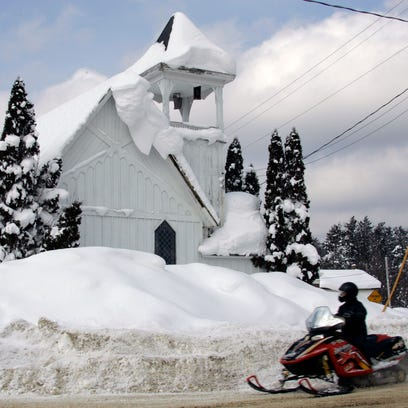 A person riding a snowmobile passes the Wesleyan Church