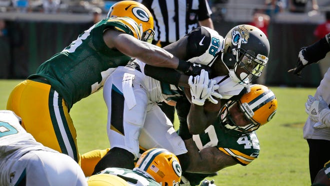 Jaguars wide receiver Allen Hurns (88) is pulled down by a swarm of Packers defenders on fourth down in the final seconds of the game Sunday in Jacksonville.