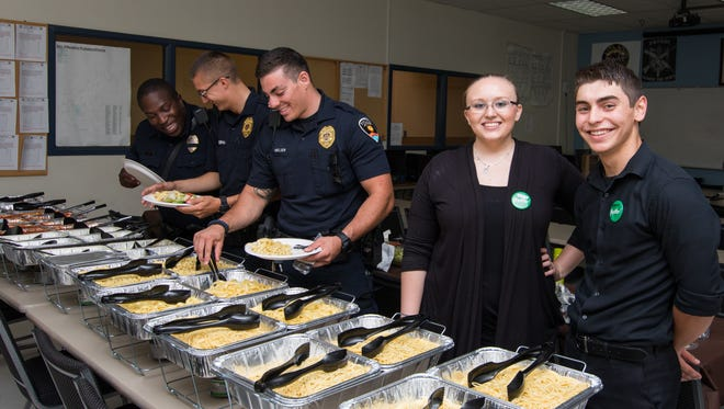 Members of the Las Cruces Police Department fill their plates during a pasta lunch Monday provided by the Las Cruces Olive Garden restaurant. Representing Olive Garden are employees Amber Auge and Estevan Herrera.