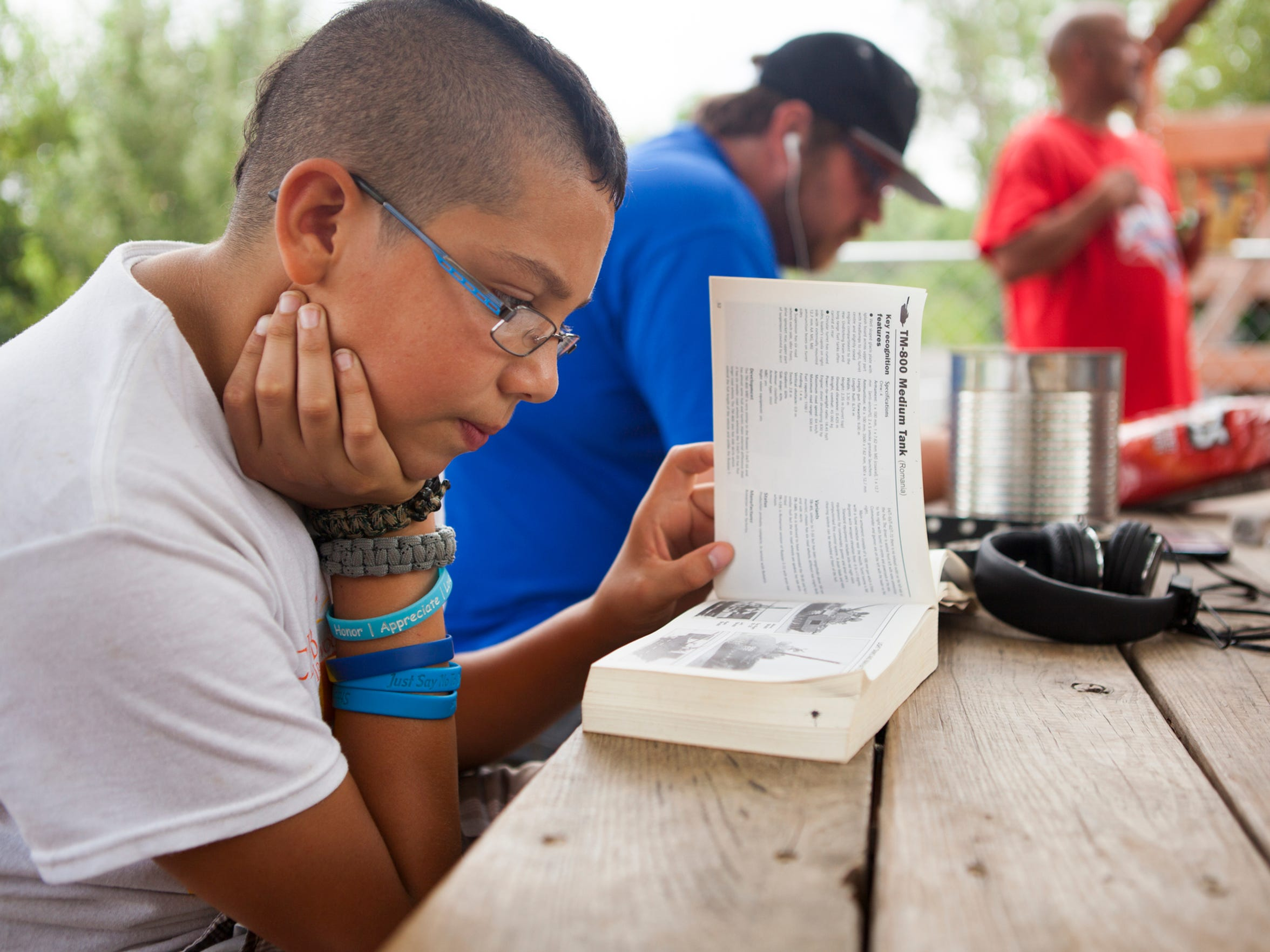 """Timothy Nettles reads a book outside The Valley Mission, relaxing with his family and other residents on Aug. 8, 2015. The 13-year-old fears people at his school finding out that he's homeless. """"They treat me differently,Ó he said. ÒThey make fun of me because I am at a shelter."""""""