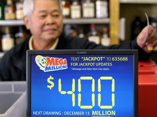 A screen displays a Mega Millions jackpot estimate as convenience store clerk Kil Dong Yeo grabs a lottery receipt in Baltimore.