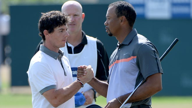 Rory McIlroy, left, and Tiger Woods shake hands after the first round of the Dubai Desert Classic.
