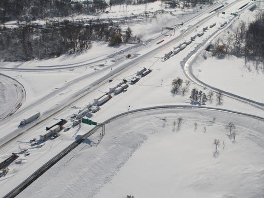 Cars and trucks are stranded by the snow on Nov. 19