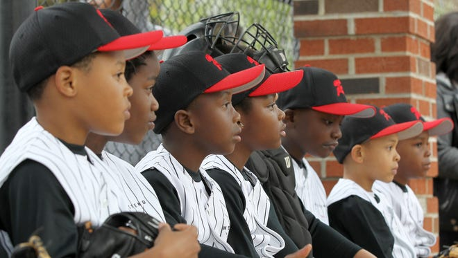 From left: Steven Sanders, 9; Antonio Penman, 8; Milton Godfrey Jr., 8; Antone Cannady, 8; Avery Battle, 9; Ozzerrian Brown, 9; and Maquel Bass, 9, look onto Weaver Field in the West End as the West End Reds prepare to take the field for a game, Wednesday, April 15.