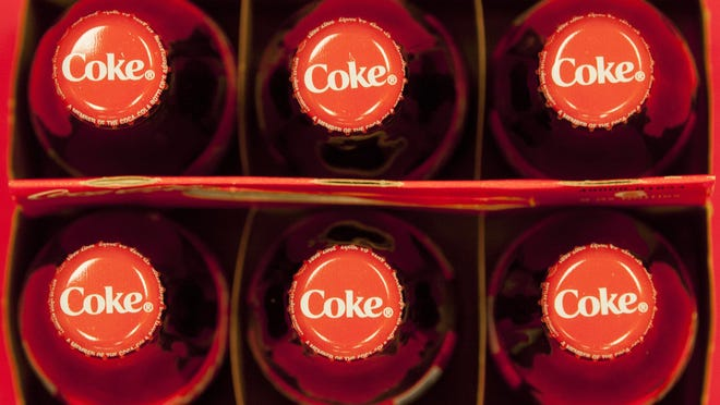 In this July 15, 2013 file photo, bottle tops of Coca-Cola 8 oz. bottles are photographed in Doral, Fla.