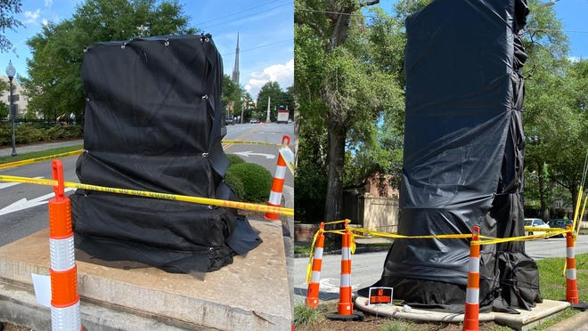 The stone bases for the George Davis monument (left) and the Confederate Memorial (right) in downtown Wilmington have now been covered with black shrouds after the statues were removed last week.