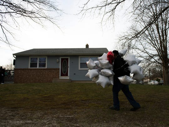 A man carries balloons to a memorial service for Phillip