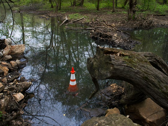 An orange cone marks the location where 3-year-old Brendan Creato's body was found in a creek off of South Park Drive in Haddon Township. The jury took a trip to the scene Thursday. Sgt. John Quigley of the Delaware River Port Authority police points out the water is deeper currently than on the day the body was found.