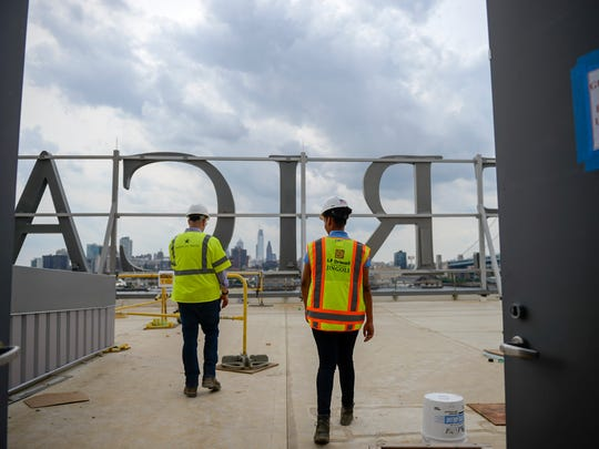 Senior project manager Jeremy Kierman, left, and assistant project manager Tyler Stokes, a Camden native, walk out by the American Water sign Friday, June 8, 2018 in Camden, N.J.