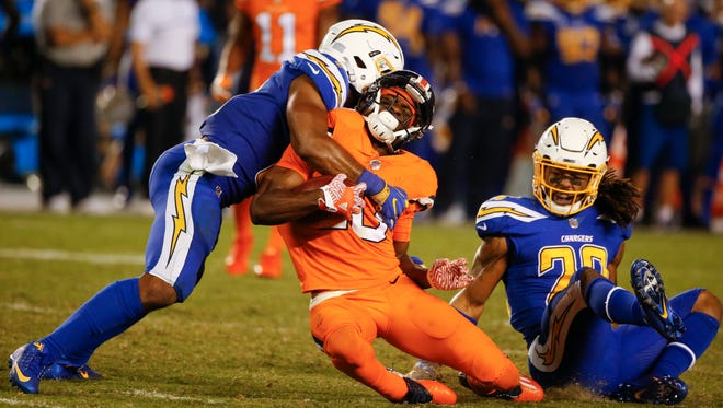 Denver Broncos wide receiver Emmanuel Sanders is hit by San Diego Chargers inside linebacker Jatavis Brown as free safety Dwight Lowery looks on during the second half of an NFL football game Thursday, Oct. 13, 2016, in San Diego.