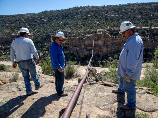 Harpole Construction Inc., workers look over a natural gas pipeline, Monday, Aug. 14, 2017 above Simon Canyon near Navajo Dam.