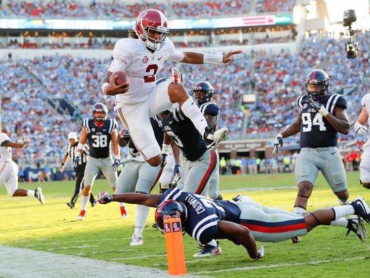 Alabama quarterback Jalen Hurts leaps over Ole Miss linebacker Terry Caldwell during the Tide's 48-43 win against the Rebels Saturday.
