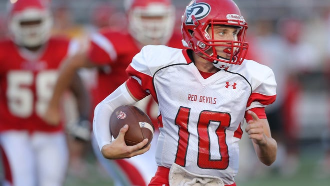 Pike quarterback Beau Trudeau looks for some running room as he scrambles out of the pocket in the first half of the game held at Fishers High School on Friday, August 29, 2014.