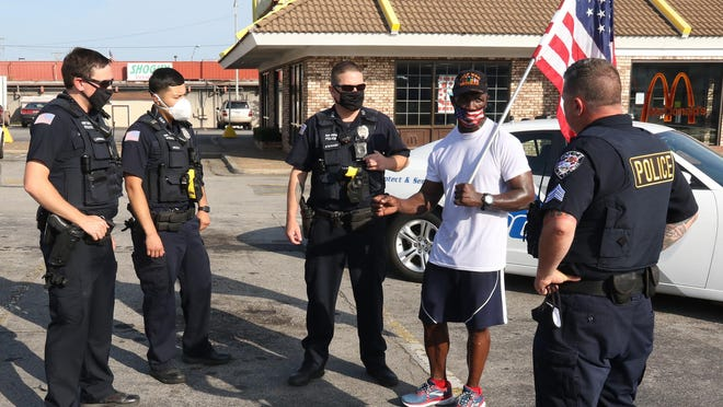 """Fort Smith police officers Jacob Landers, from left, Alex Meza, Jeff Stewart and Sgt. Lee McCabe meet with Army Veteran Nate Thomas, Saturday, July 18, 2020, after Thomas completed his 10-mile run in Fort Smith as a leg in his """"Run For America Tour,"""" across Arkansas. Thomas runs 10-miles each Saturday in major Arkansas cities, """"encouraging everyone to stay strong during the COVID-19 pandemic."""" Thomas started his journey March 11, 2020, in his hometown of Forrest City and said he will run 10 miles each Saturday in an Arkansas city until the pandemic is over, encouraging everyone he meets to """"fight the good fight."""""""