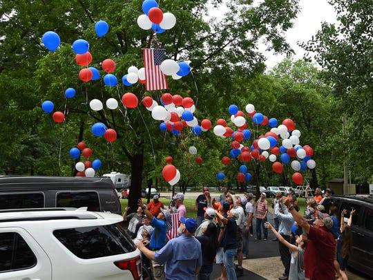 Veterans and volunteers release red, white and blue balloons on Monday afternoon after a fishing trip and cookout for paralyzed veterans.