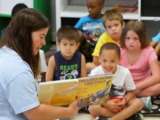Jillian reads to children in a kindergarten camp at