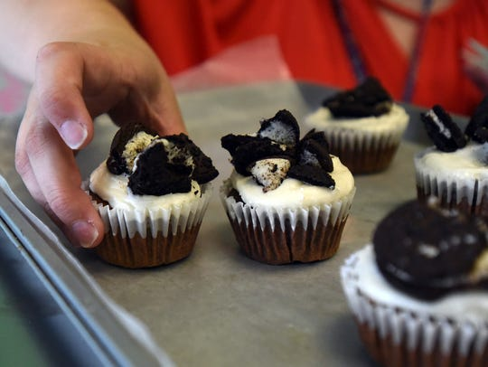 Madison Welker moves cookies and creme cupcakes to