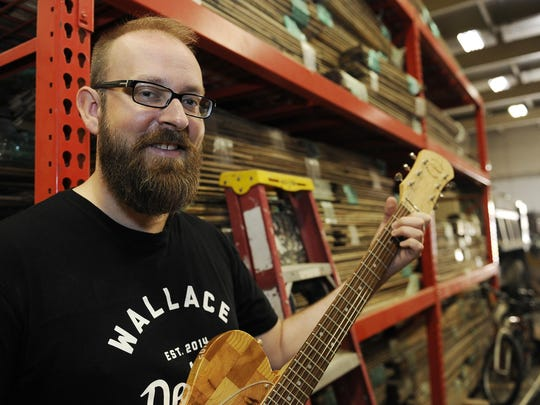 Mark Wallace, CEO of Wallace Detroit Guitars, holds a guitar that was made from used reclaimed wood.