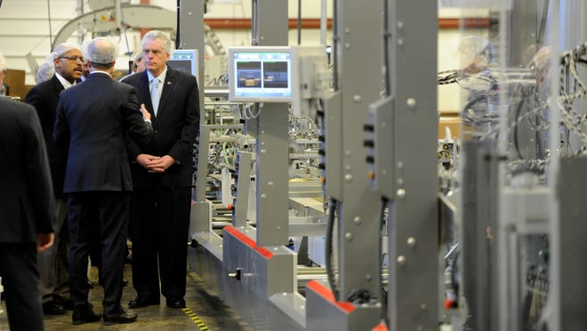 Murry Pitts, General Manager at Graphics Packaging International gives a tour to Maurice Jones, Virginia Secretary of Commerce and trade and Governor, Terry McAuliffe during their economic development announcement at their plant in Staunton, Friday, Feb. 26, 2016.