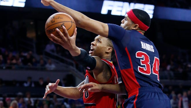 Portland Trail Blazers' Damian Lillard (0) goes to the basket against Detroit Pistons' Tobias Harris (34) during the second half of an NBA basketball game on Sunday, March 6, 2016, in Auburn Hills, Mich. The Pistons defeated the Trail Blazers 123-103.