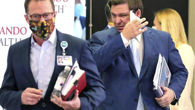 Florida Gov. Ron DeSantis, right, removes his face mask as he arrives Sunday for a news briefing on the state's status in the coronavirus crisis, at Orlando Health's Orlando Regional Medical Center. DeSantis is arriving with Orlando Health President & CEO David Strong, left.