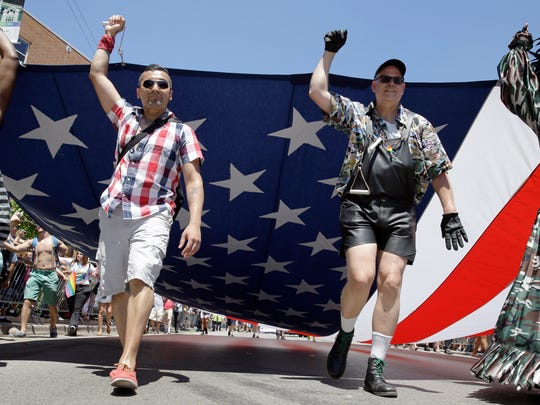 Members of the Gay, Lesbian and Bisexual Veterans Association march with a big U.S. Flag at the 45th Annual Chicago Pride Parade during the parade on Broadway in Chicago, Sunday, June 29, 2014. The event, the first since Illinois' law allowing same-sex marriage went into effect, has 200 registered entrants, with about 1 million expected to participate.