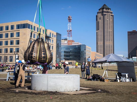 "Against the downtown skyline, DSM Art Center workers install Tuesday, Feb. 27, 2018, the aptly named â""Pumpkin Largeâ"" by Yayoi Kusama, at the John and Mary Pappajohn Sculpture Park in downtown Des Moines, Iowa."