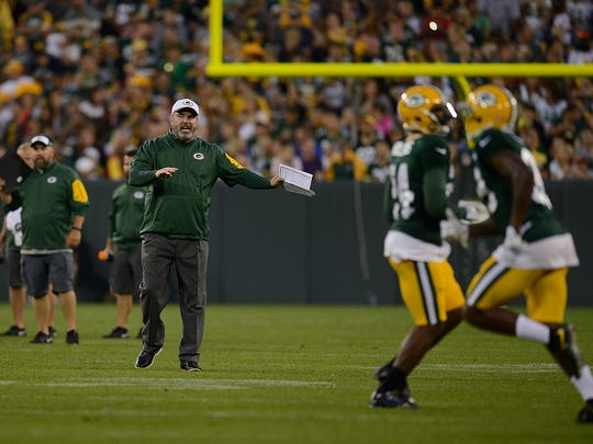 Green Bay Packers coach Mike McCarthy shouts instructions to his players during Packers Family Night at Lambeau Field on Saturday, Aug. 8, 2015.
