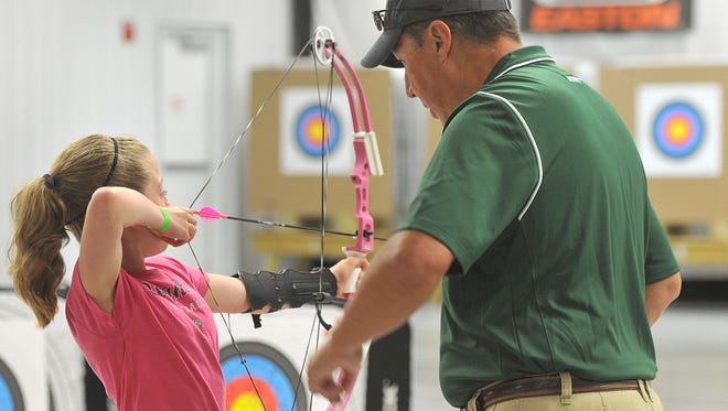 Brooke Smith, 10, from the 4-H Nature Trackers in Portland gets some one-on-one instruction on how to use a compound bow from MSU Archery Coach Glen Bennett, Saturday during the Demmer Center's Olympic Day.