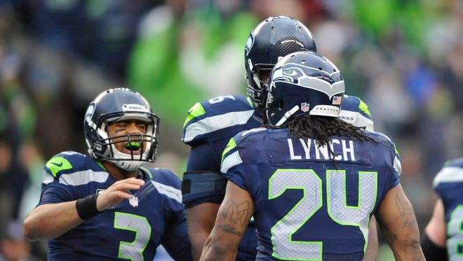Russell Wilson (3) congratulates running back Marshawn Lynch (24) for scoring a touchdown against the New Orleans Saints during the first half of the 2013 NFC divisional playoff game.