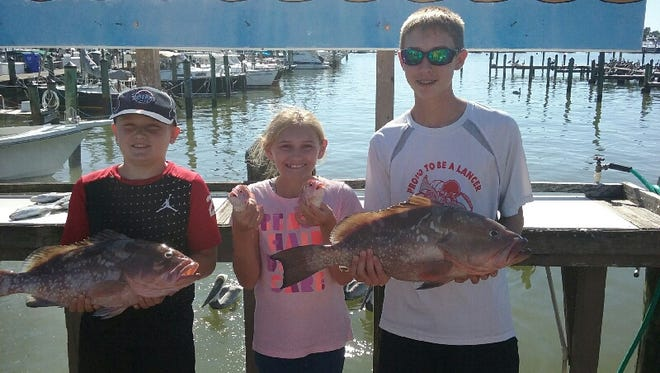 Alex Toothman (left), Katy Behnke and Patrick Behnke of Stevensville, Michigan, caught red grouper and white grunts, while fishing on the charter boat Capt. Marvel during their Christmas break from school.