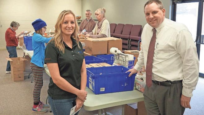 Tiger Packs recently received a gift from Key Coop. Shown are Amy Van Weeldon, Key Coop, and Ryan Benz, Tiger Packs Advisory Committee member, with packagers in the background.