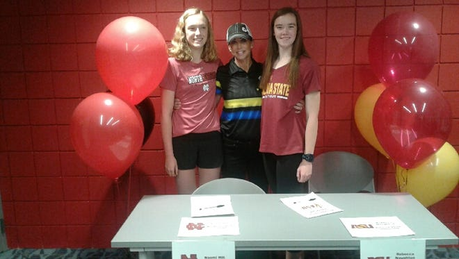 Z3 coach Jenny Weber, center, joins Naomi Hill, left, and Rebecca Naughton at their college signing day ceremony Tuesday at the Wellmark YMCA.