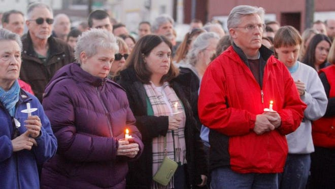 People stand with candles April 1 during the candlelight memorial service for Officer David W. Smith.