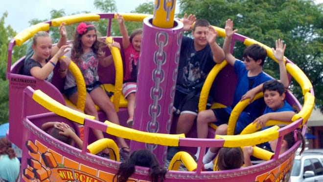 Kids spin around with arms up on a carnival ride at the Founders Fest.