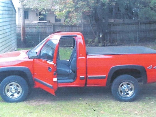 The vehicle is a 2001 red Chevrolet pickup with a black cover on its bed. The license plate number is CGN-7187.