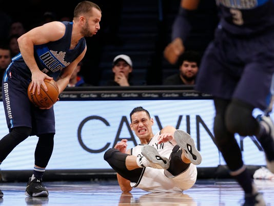 Brooklyn Nets guard Jeremy Lin (7) winces on the floor in the first half of an NBA basketball game against the Dallas Mavericks, Sunday, March 19, 2017, in New York. (AP Photo/Kathy Willens)