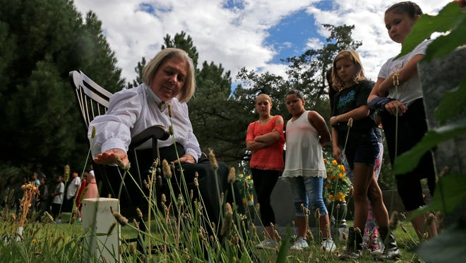 D'Ann Waters points to the gravestone of Lillie Johnson during a dress rehearsal last year for Dining with the Dead event at Greenlawn Cemetery in Farmington.