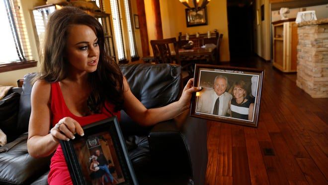 Summer Jakino-Whistle shows photos of her father, Michael Jakino, and her mother, Robin Jakino, during an interview July 11 at her home in Crouch Mesa. Michael Jakino was killed in a crash in September 2015, and Robin Jakino was severely injured.