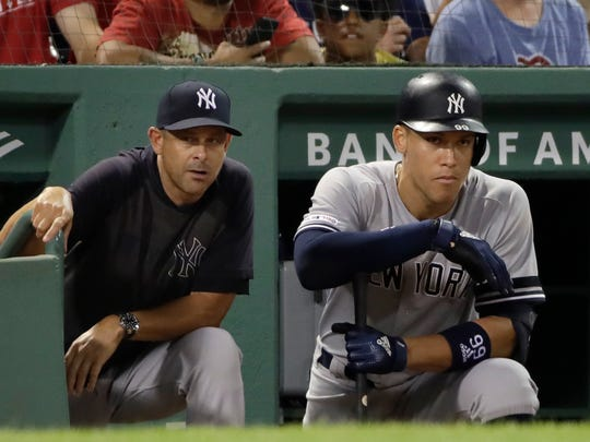 New York Yankees manager Aaron Boone, left, and right fielder Aaron Judge watch from the dugout in the ninth inning of a baseball game against the Boston Red Sox at Fenway Park, Friday, July 26, 2019, in Boston. (AP Photo/Elise Amendola)