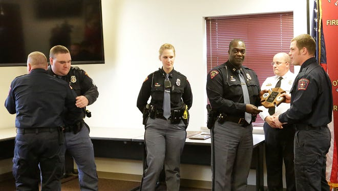 City of Fond du Lac Fire and Rescue members Brian Westby (far left) and Phillip Seibel (far right) are given awards and congratulated by Wisconsin State Patrol members Andrew Hyer, Clarissa Justmann and Captain Anthony Burrell, as well as Fire Chief Peter O'Leary Thursday April 7, 2016, for their roles in providing life support measures to Trooper Trevor Casper who was shot March 24, 2015.