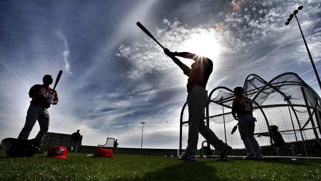 Reds players warm up before batting practice at spring training in Goodyear.