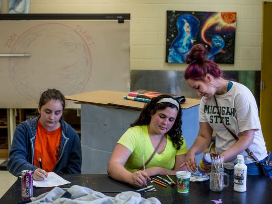 Middle school students Jada Schuler, 13, Anna Miler, 13, and Riverview East student Holly Stuart, 17, work together on homework and art projects as part of a mentoring program Friday, June 2, 2017 at Riverview East High School.