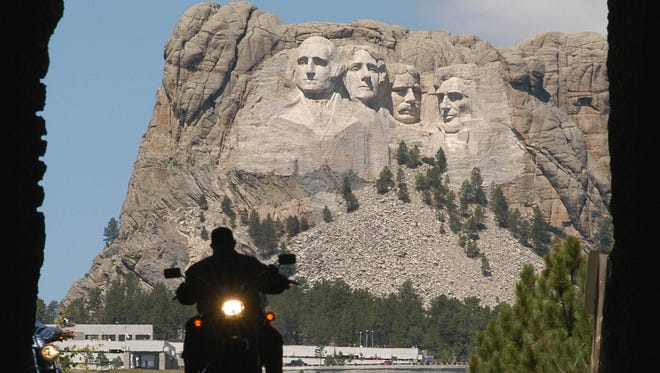 A biker rolls through a tunnel on Iron Mountain Road as Mount Rushmore stands in the background Wednesday, Aug. 11, 2004, near Keystone, S.D. Authorities said this year's Sturgis Motorcycle Rally is drawing bigger crowds that have been more well-behaved than in previous years. Mount Rushmore National Memorial is seeing a 4 percent jump in visitors compared to last year, and rally-related visitation to the site is on pace to set an all-time record, said Chief Ranger Mike Pflaum. (AP Photo/Doug Dreyer)