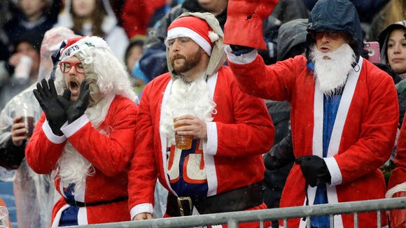 fans dressed in santa claus suits watch an nfl football game between the new england patriots - Football Games On Christmas