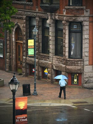 A pedestrian travels Wednesday along St. Germain Street with umbrella in hand as the rain fell over the lunch hour.